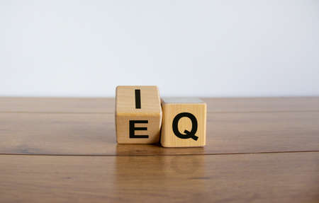 Photo for Wooden cubes with the expression 'IQ' 'Intelligence Quotient' to 'EQ' 'Emotional Intelligence Quotient'. Wooden table. Business concept, copy space. Beautiful white background. - Royalty Free Image