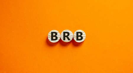 Foto de Wide view image of BRB abbreviation spelled on wooden circles. Placed over beautiful orange background, copy space. Business concept. - Imagen libre de derechos