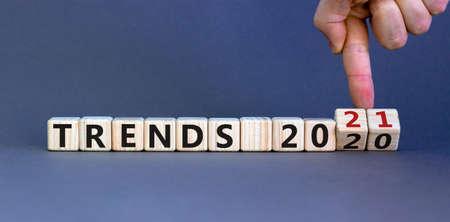 Foto de Business concept of planning 2021. Male hand flips wooden cubes and changes the inscription 'TRENDS 2020' to 'TRENDS 2021'. Beautiful gray background, copy space. - Imagen libre de derechos