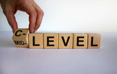 From mid level to C level. Hand turns a cube and changes the words 'mid level' to 'C level'. Beautiful white background, copy space. Business concept.