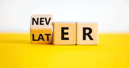 Photo pour From later to never symbol. Turned a cube and changes the word 'later' to 'never'. Beautiful yellow table. White background. Busines and later to never concept. - image libre de droit