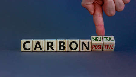 Photo for From carbon positive to neutral. Hand flips cubes and changes words 'carbon positive' to 'carbon neutral'. Beautiful white background, copy space. Business, ecological and carbon neutral concept. - Royalty Free Image