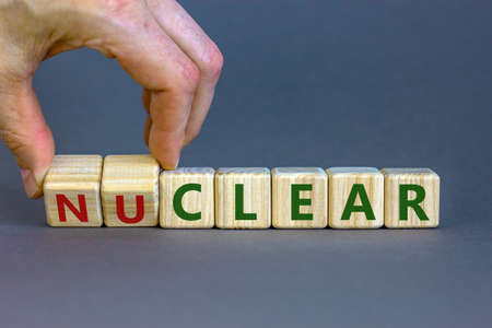 Photo for Nuclear or clear symbol. Businessman turns a cube and changes the word 'nuclear' to 'clear'. Beautiful gray background. Nuclear or clear and business concept. Copy space. - Royalty Free Image