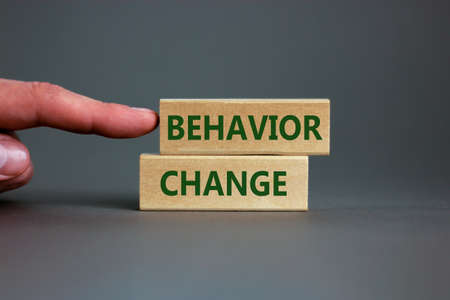 Time to behavior change symbol. Wooden blocks with words \'behavior change\'. Beautiful gray background. Businessman hand. Copy space. Business, psychology and behavior change concept.
