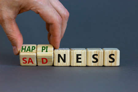 Photo pour Happiness or sadness symbol. Businessman turns cubes and changes the word 'sadness' to 'happiness'. Beautiful gray background. Business, psychological and happines or sadness concept. Copy space. - image libre de droit