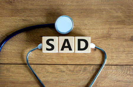Photo pour SAD, social anxiety disorder symbol. Concept words 'SAD, social anxiety disorder' on cubes on a beautiful wood background. Medical, psychological and SAD, social anxiety disorder concept. Copy space. - image libre de droit