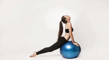 Portrait of young attractive woman doing exercises. Brunette with fit body holding fitness ball. Series of exercise poses.