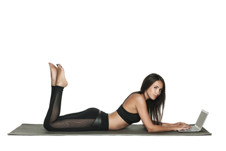 Young woman working on her laptop while lying on a mat in yoga class. Busy woman combines work and fitness. Isolated on white.
