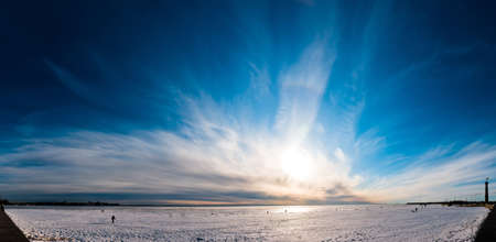 Beautiful cloudy and blue sky panorama over ice lake in Saint-Petersburg, Russia