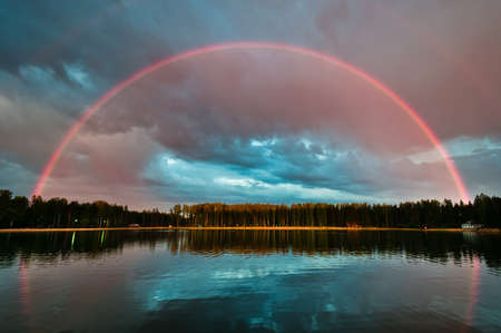 Photo pour Full beautiful rainbow arc over the lake with still water - image libre de droit