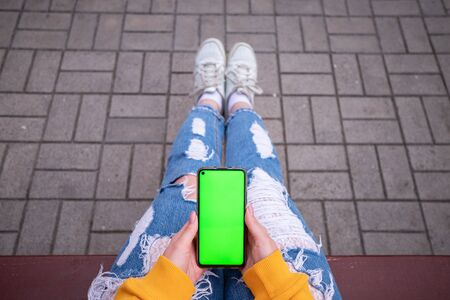 Photo pour Young girl in a yellow sweater holds a phone with a green screen - image libre de droit