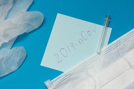 Photo pour Novel coronavirus disease called 2019-nCoV handwriting on blue paper. protective mask and surgical gloves on blue background - image libre de droit