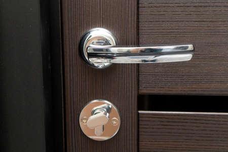 Photo for Door metal handle for a wooden door. - Royalty Free Image
