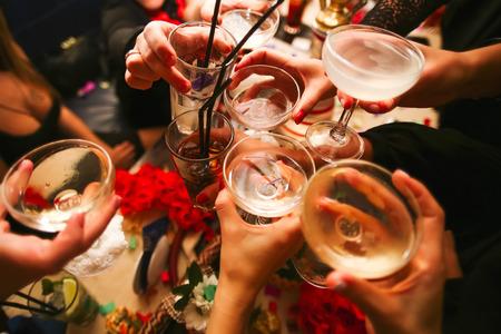 Foto de Clinking glasses with alcohol and toasting, party - Imagen libre de derechos