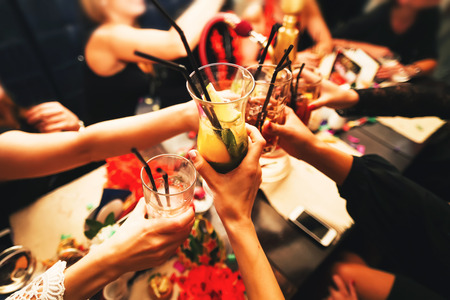 Foto de Clinking glasses with alcohol and toasting, party. Congratulations to the event. Cheerful party friends - Imagen libre de derechos