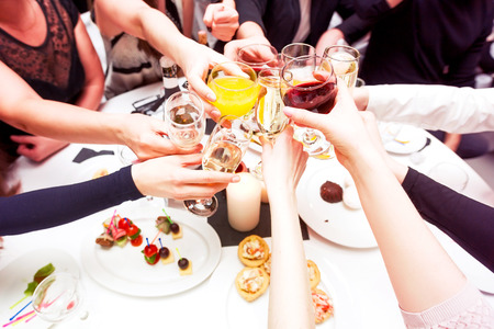 Clinking glasses with alcohol and toasting, party. Congratulations to the event. Cheerful party friends