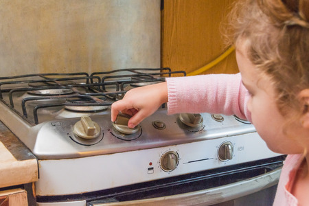 Foto de girl, a child includes a gas stove in the absence of adults, the risk of poisoning, fire, explosion - Imagen libre de derechos