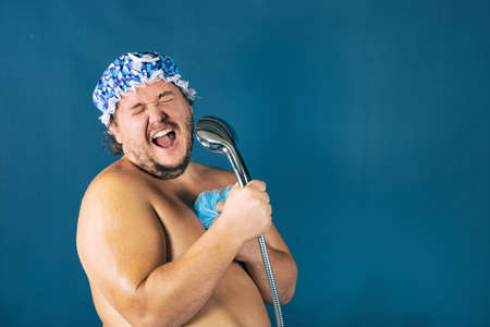 Photo for Funny fat man in blue cap sing in the shower. Fun and cleanliness - Royalty Free Image