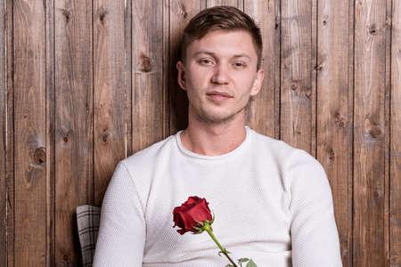 Photo pour Young handsome man sitting near wood wall - image libre de droit