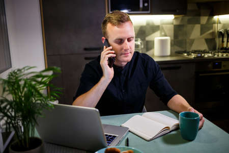 Foto de businessman working with laptop, work from home, thoughtful and worried about the future, talking on the phone, stock market trends, messages, virus quarantine time - Imagen libre de derechos