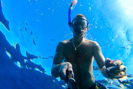 Photo pour A guy with a mask and snorkel dives into the blue water of the Red Sea and photographs himself - image libre de droit