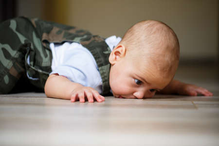 Photo for little boy aged 8 months in overalls, a white shirt and white socks crawling on the floor and smiling - Royalty Free Image
