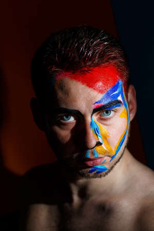 Photo for Portrait of a young man with colored paint on a dark background. Professional Makeup Fantasy Art Makeup - Royalty Free Image