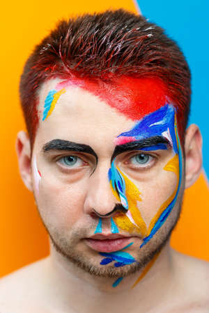 Photo for Makeup on the skin. Portrait of a young man with colored paint on a yellow background. Professional Makeup Fantasy Art Makeup - Royalty Free Image