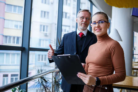 Photo pour Girl manager in her own office tells a successful new business plan for economic development to her teacher mentor boss. Holds a folder with important documents in his hands. - image libre de droit