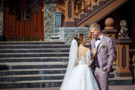 Photo pour The bride in a white wedding dress and groom in a suit on the background of a brick building with large steps - image libre de droit