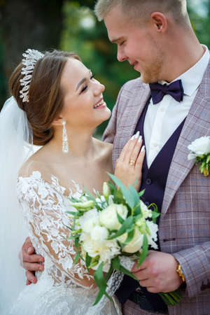 Photo pour Bride in white dress and groom in costume cuddle and walk in the park - image libre de droit