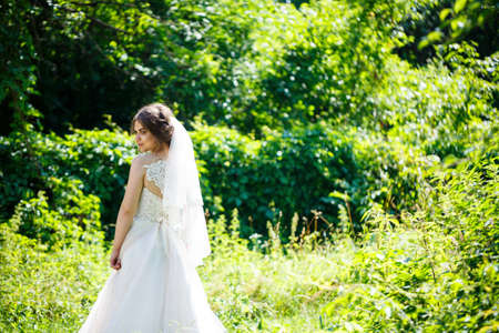 Photo pour Happy girl bride in a long white wedding dress and in a veil swirl in a green park on nature. - image libre de droit