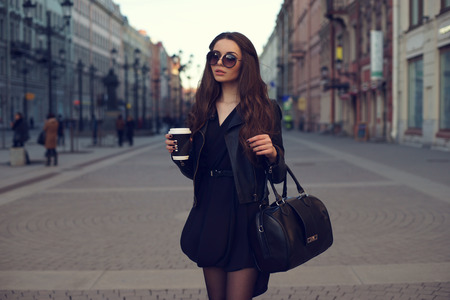 Photo pour Young beautiful pretty girl walking along the street with handbag and cup of coffee. - image libre de droit