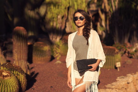 Foto de Stylish trendy beautiful girl with long braid posing in t-shirt and shorts with handbag against cactuses. Outdoor summer portrait - Imagen libre de derechos