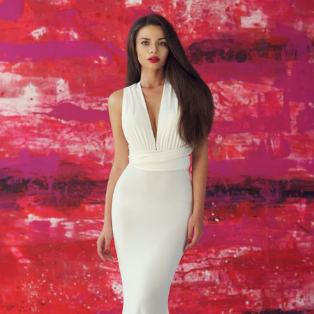 Young beautiful stunning woman posing in long elegant white evening dress and red shoes against stylish red background