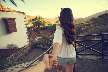 Photo pour Beautiful girl holding mans hand and leading him. Love and travel concept. Beautiful tropical landscape. - image libre de droit