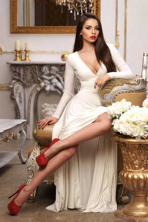 Foto de Vogue fashion style portrait of young beautiful pretty elegant rich woman wearing evening dress and sitting on armchair in luxury apartments - Imagen libre de derechos