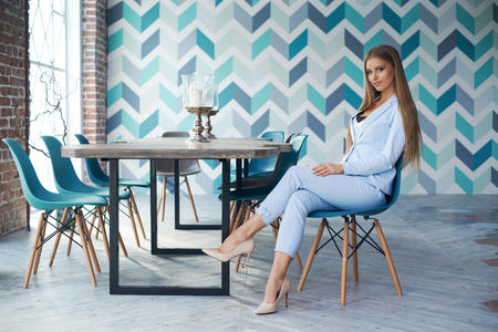 Young beautiful woman with long straight blond hair in blue suit sitting at wooden table in stylish modern interior. Natural lightning
