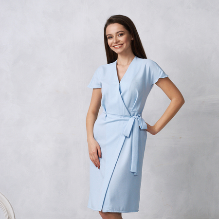 Foto de Attractive woman with long brunette hair dressed in fashionable blue wrap around midi dress with short sleeves smiling and posing. Laughing female model standing against white wall on background. - Imagen libre de derechos