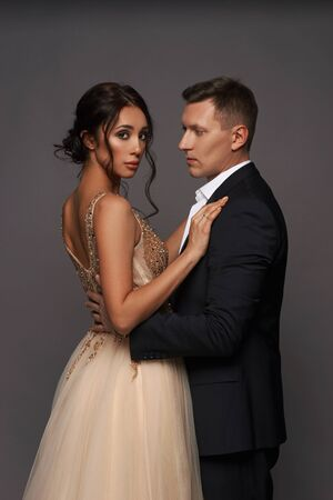 Photo pour Attractive beautiful and well-dressed young adult couple posing in studio on gray background. Woman in beautiful evening dress and man wearing black classical suit with white jacket - image libre de droit