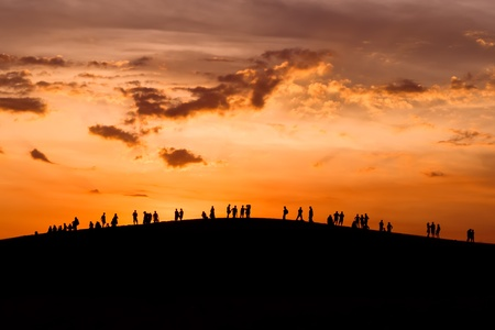 Group of people enjoying the sunset on hill