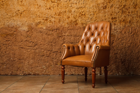 Leather armchair against stone wall. Vintage armchair in loft.