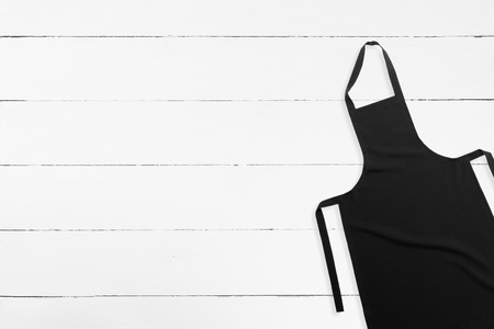 Blank black apron on white wooden background with copy space
