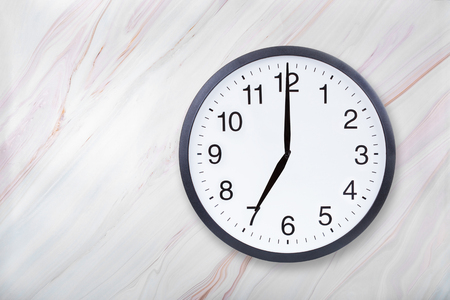 Photo for Wall clock show seven oclock on marble texture. Office clock show 7pm or 7am on marble texture with natural pattern - Royalty Free Image