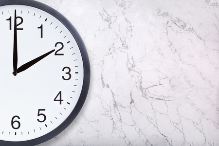 Foto de Closeup of wall clock show two oclock on white marble texture. Office clock show 2pm or 2am on marble background. Crop image - Imagen libre de derechos