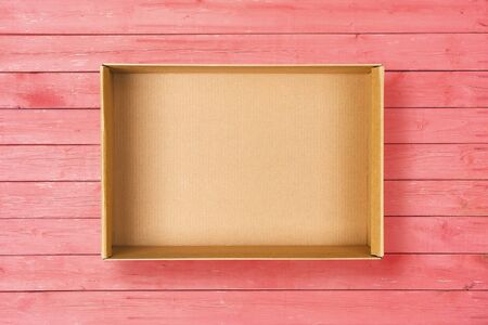 Photo for Open cardboard box on pink background. Empty cardboard package on pink wooden texture. Flat lay - Royalty Free Image