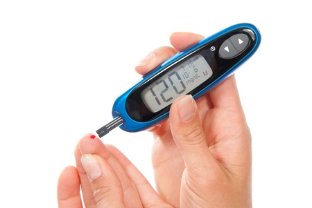 Diabetes patient measuring glucose level blood test using ultra mini glucometer and small drop of blood from finger and test strips. Device show 120