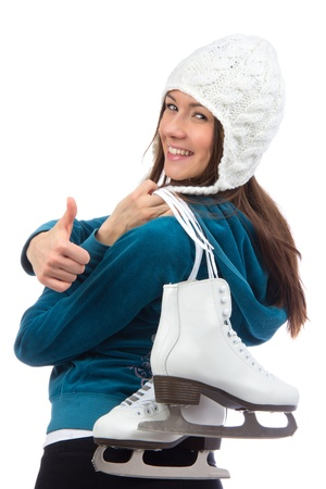 Young woman woman with  ice skates for winter ice skating sport activity in white hat smiling ang thumb up isolated on a white background