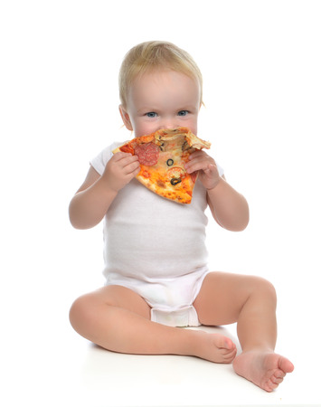 Infant child baby toddler sitting enjoy eating slice of pepperoni pizza with tomatoes cheese isolated on a white background