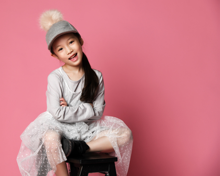 Nicely smiling asian fashion kid girl in pink dress and funny cap with fur pompon on pink background with free text space